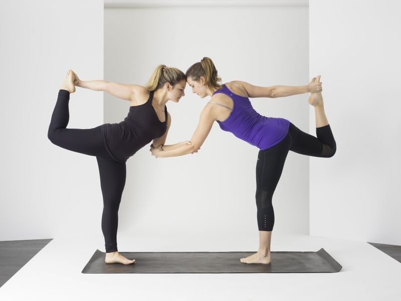 two women performing a complicated yoga position
