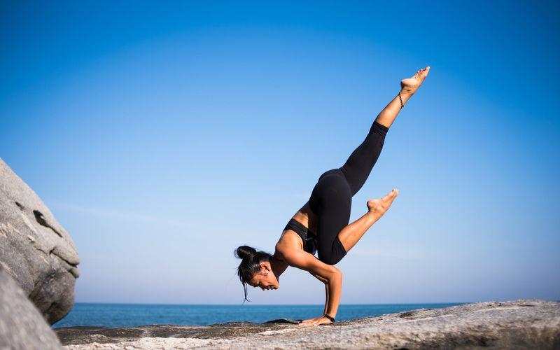 woman in yoga pose on the beach black leggings