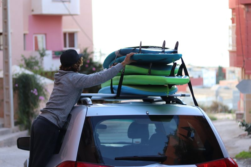 a guy arranging surf boards on a car