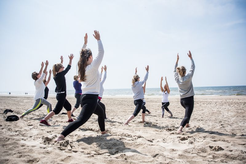 a group of yogis at the beach