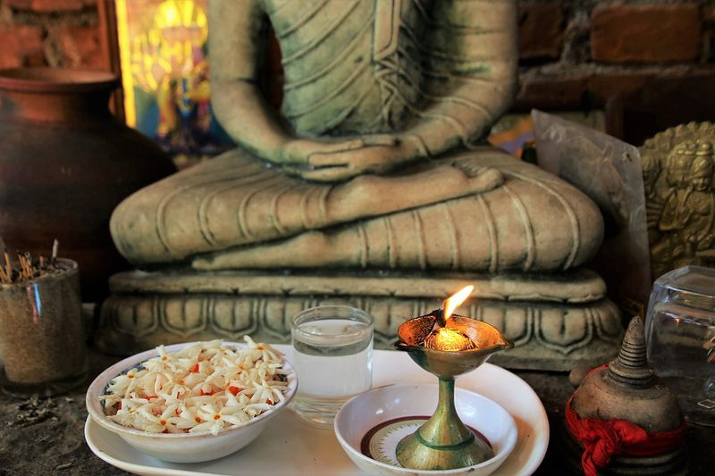 Buddha statue with flowers and candle