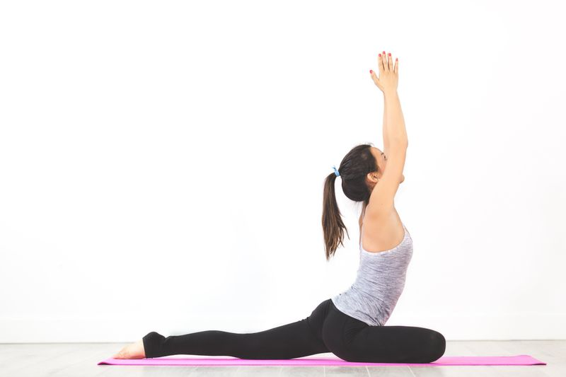 girl practicing yoga on pink yoga mat